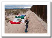 American photographer, peace activist and educator Raechel Running at the border fence in Agua Prieta, Mexico, where she continuously works with a local community. <br /> <br /> <br /> This picture is part of my long-term project<br /> LA FRONTERA: Artists along the US Mexican Border.<br /> &copy; Stefan Falke / www.stefanfalke.com