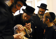 In Stamford Hill, London, United Kingdom on the 3rd birthday of a Orthodox Jewish boy he has his first ever hair cut leaving his peyos (sideburns) to grow. Here his father carefully shaves his head watched closely by his extended family. He will now begin to learn the Torah.