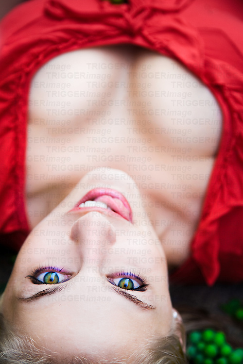 Blond girl laying on the ground, licking lips