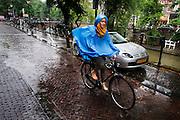 In Utrecht fietst een meisje op blote voeten door de regen.<br /> <br /> In Utrecht a girl is cycling barefoots in the rain.