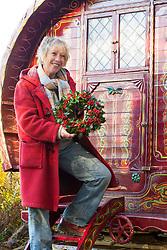 Carol Klein with holly wreath in front of gypsy caravan. Ilex