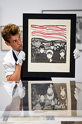"© Licensed to London News Pictures. 12/09/2019. LONDON, UK.  A technician presents a lithograph by Edvard Munch at a photocall for ""Les Peintres-Graveurs"", a multi-artist portfolio of lithographs published in 1896 by Ambroise Vollard, to be auctioned at Sotheby's on September 17 with an estimate of £500,000 to £1,000,000.  It is the only known complete example and includes 22 prints by the greatest Impressionist and Post-Impressionist artists such as Pierre Bonnard, Odilon Redon, Théo van Rysselberghe, Auguste Renoir, and Edouard Vuillard., as well as the first colour lithograph by a then not so well-known Edvard Munch.  Photo credit: Stephen Chung/LNP"