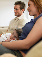 Girl (3-4) watching television with parents on couch