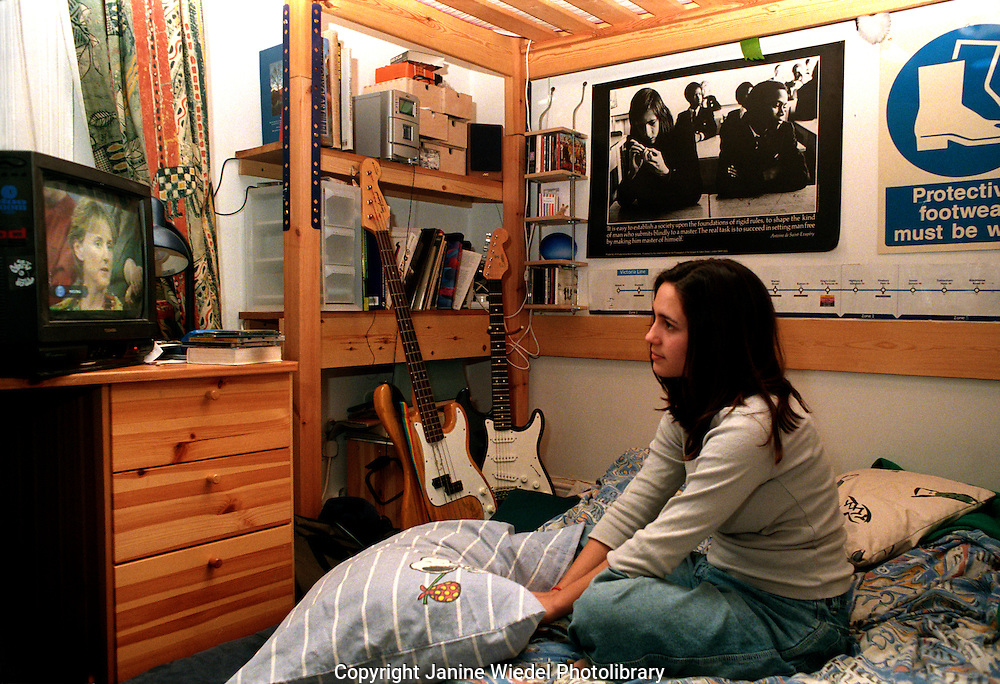 Teenaged girl sitting on the bed in her room watching television.