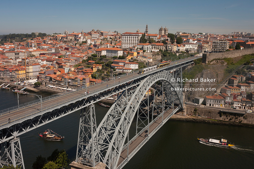 A morning aerial panorama of boats about to pass under, while a tram crosses over the Ponte de Dom Luis I bridge with the city of Porto behind on the River Douro and a foreground of warehouse rooftops, on 20th July, in Porto, Portugal. The Dom Luís I (or Luiz I) Bridge is a double-decked metal arch bridge that spans the Douro River between the cities of Porto and Vila Nova de Gaia in Portugal. At the time of construction its span of 172 m was the longest of its type in the world. (Photo by Richard Baker / In Pictures via Getty Images)