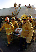 Firemen carry a victim away from the train tracks. Behind them, rescue workers work to remove victims who were traped inside the wreckage of a MetroLink commuter train that collided with a freight train in Chatsworth, California that claimed 25 lives on Friday, Sept. 12, 2008. Photo by John McCoy/staff photographer.