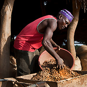 Athman Omari, an artisanal gold miner collects rocks that will be ground to dust in order to extract gold, at a local mine outside of Geita.