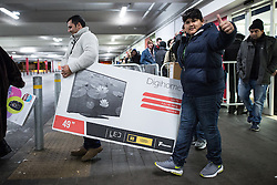 © Licensed to London News Pictures . 27/11/2015 . Salford , UK . Two people carrying a 49 inch television from a branch of Tesco in Pendleton , Salford , this morning (Friday 27th November) as people behind queue for Black Friday offers . Last year (2014) scuffles and fights were reported amongst queuing bargain-hunters . Photo credit: Joel Goodman/LNP