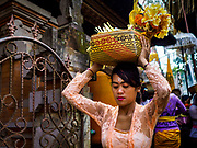 "02 AUGUST 2017 - UBUD, BALI, INDONESIA: People leave the temple after making an offering during the ""Merchants' Day"" ceremony at the Pura (Temple) Melanting Pasar Ubud, the small Hindu temple in the Ubud market. It's a day that merchants throughout Ubud come to the temple to make offerings and pray for prosperity.    PHOTO BY JACK KURTZ"