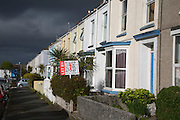 Terraced housing with letting signs  in Falmouth, Cornwall, England, UK with storm clouds overhead