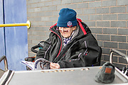 A Bolton Wanderers fan reads the match day programme outisde the University of Bolton stadium before the EFL Sky Bet League 1 match between Bolton Wanderers and Milton Keynes Dons at the University of  Bolton Stadium, Bolton, England on 16 November 2019.