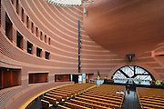 Nave of Evry Cathedral of the Resurrection, or Cathedrale de la Resurrection d'Evry, seen from the first floor, designed by Mario Botta and built 1992-95, Evry, Essonne, France. The nave is housed within a cylindrical concrete tower, lined with handmade red bricks. Light floods in from the glass around the top of the walls, and the floor is in black granite. The white marble altar stands in front of a window with a tree design, and the crucifixion sculpture above is from Tanzania. The cathedral was opened in 1995, and consecrated and dedicated to St Corbinian in 1996. Picture by Manuel Cohen