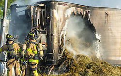 April 28, 2017 - Palm Beach, Florida, U.S. - Hay spills out as firefighters battle a tractor trailer fire on the Florida Turnpike Friday morning. (Credit Image: © Lannis Waters/The Palm Beach Post via ZUMA Wire)