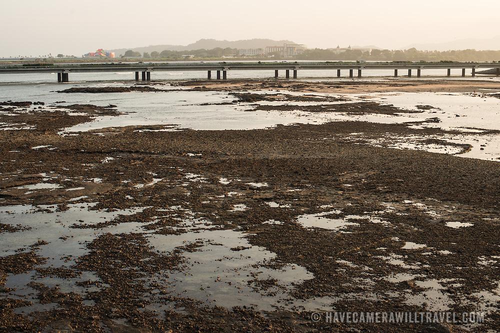 Low tide on the rocky flats on the waterfront of Casco Viejo, Panama City, Panama, on Panama Bay.