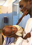 (FILE) Picture dated 20 october 2004 of Musif, an 18month old Sudanese IDP (internally displaced people) boy suffering from severe malnutrition and Tuberculosis reaching out to his father in the theraputic feeding centre at the Nyala hospital in south Darfur, Sudan. The UK-based charity Save the Children anounced Tuesday 21 December 2004 it is pulling out of the Darfur region of western Sudan after attacks which have killed four of its staff.The latest attack on 'Save the Children' saw two of its 350-strong Darfur team shot dead on a highway  in clearly-marked humanitarian vehicles on 12 December 2004 whilst thousands of displaced Sudanese continue to pour into refugee camps amidst continued fighting.