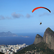 A tandem para glider flying above the hillside of Pedro Bonita high in the hills of Rio de Janeiro. Pilots of hang gliders and para gliders take tourists for tandem flights with breathtaking views of the city before landing on Sao Conrado beach. Rio de Janeiro,  Brazil. 9th September 2010. Photo Tim Clayton.