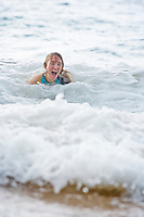 Woman laughing and having fun in the foam of a wave that just hit her and washed her up on Maluaka beach, Maui Hawaii