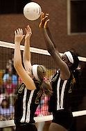 """6 Oct. 2011 -- ST. LOUIS. -- Rosati-Kain High School volleyball players Oluwashayo Oginni (23) and Maggie Griffin (26) stop a shot by Bishop DuBourg High School during a special """"pink game"""" between the schools at DuBourg Thursday, Oct. 6, 2011. The """"pink game"""" to benefitted SSM St. Mary's Health Care Center's Cancer Care, in honor of Rosati-Kain president Sister Joan Andert, SSND, who is currently undergoing treatment for breast cancer. Photo © copyright 2011 Sid Hastings."""