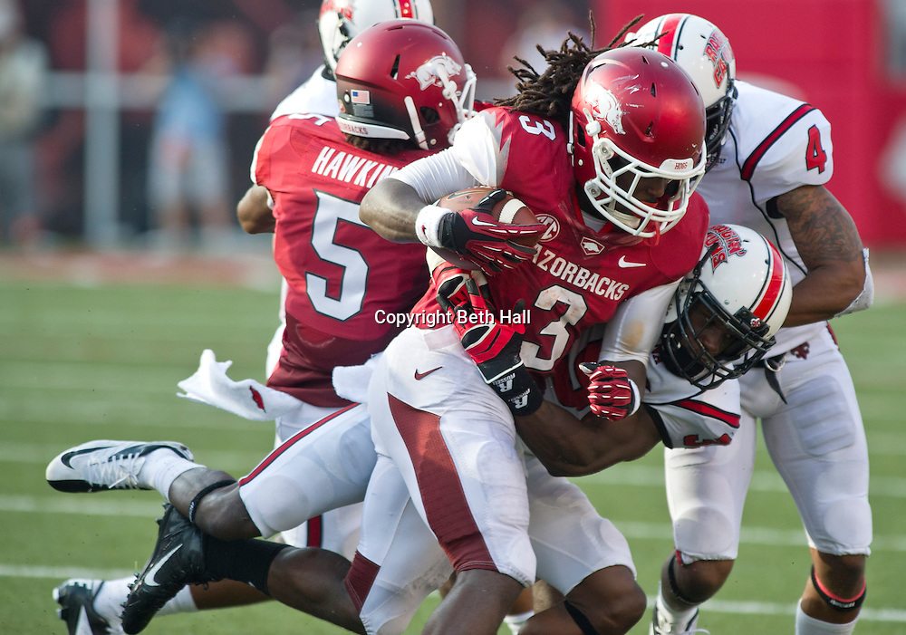 Aug 31, 2013; Fayetteville, AR, USA; Arkansas Razorback running back Alex Collins (3) is brought down Louisiana Ragin' Cajuns linebacker Chris Hill (39) and safety Trevence Patt (4) during the second half of a game at Donald W. Reynolds Razorback Stadium. Arkansas defeated Louisiana 34-14. Mandatory Credit: Beth Hall-USA TODAY Sports
