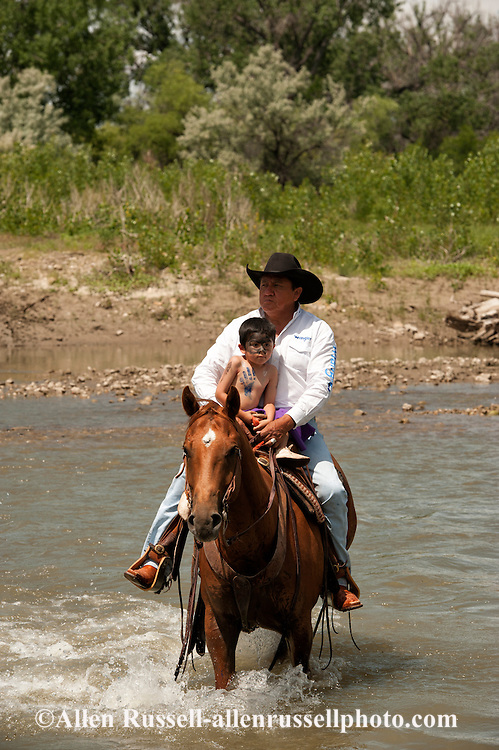 Kennard Real Bird crosses Little Bighorn River with grandson Braxton, Battle of the Little Bighorn Reenactment,  Montana