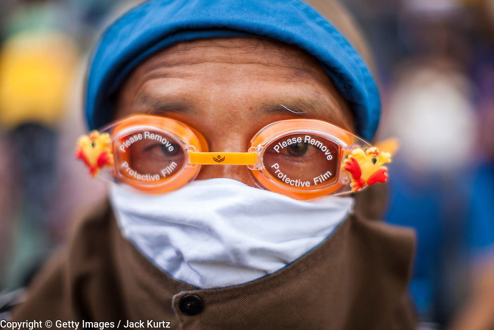 24 NOVEMBER 2012 - BANGKOK, THAILAND:  A man with swim goggles and breathing mask to offset the effects of tear gas used by Thai riot police during a large anti government, pro-monarchy, protest  on November 24, 2012 in Bangkok, Thailand. The Siam Pitak group, which sponsored the protest, cited alleged government corruption and anti-monarchist elements within the ruling party as grounds for the protest. Police used tear gas and baton charges againt protesters.       PHOTO BY JACK KURTZ