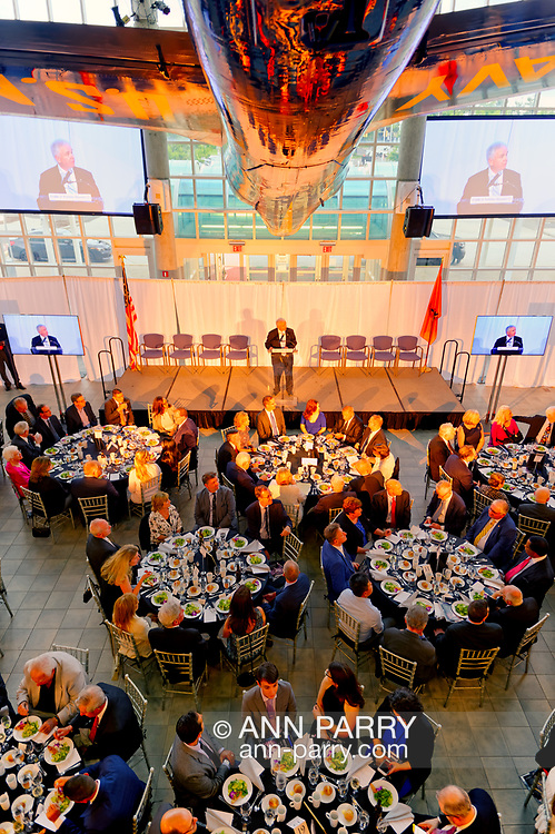 Garden City, New York, U.S. June 6, 2019. ANDY PARTON, President of Cradle of Aviation, is speaking on stage, as seen from second level of atrium of Cradle of Aviation Museum, during Apollo at 50 Anniversary Dinner, an Apollo astronaut tribute celebrating the Apollo 11 mission Moon landing. The 5 Apollo Astronauts, 2 Apollo Flight Commanders, and Nassau County Executive LAURA CURRAN sat at tables next to stage. U.S. Navy Blue Angels Grumman F-11A Tiger jet is suspended from ceiling.