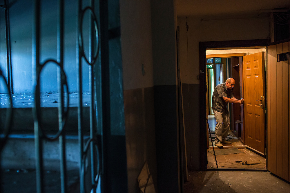 A man fixes his door after the apartment building was hit by a suspected grad rocket strike on Tuesday, July 29, 2014 in Donetsk, Ukraine.