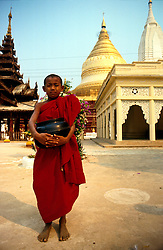 BURMA PAGAN MAR95 - A buddhist novice monk holds on to his laquered rice bowl as he goes on his obligatory daily round of begging. In buddhist tradition, novices, once initiated, retain their lifelong right to return to a monastic lifestyle whenever they wish. .. jre/Photo by Jiri Rezac. . © Jiri Rezac 1995. . Contact: +44 (0) 7050 110 417. Mobile: +44 (0) 7801 337 683. Office: +44 (0) 20 8968 9635. . Email: jiri@jirirezac.com. Web: www.jirirezac.com