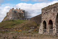 Lindisfarne Castle partially clad in scaffolding as it undergoes major restoration works, with the lime kilns in the foreground. Holy Island, Northumberland, England, UK<br />