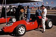 Pete Lyons engrossed in F1 car at 1960 US Grand Prix at Riverside