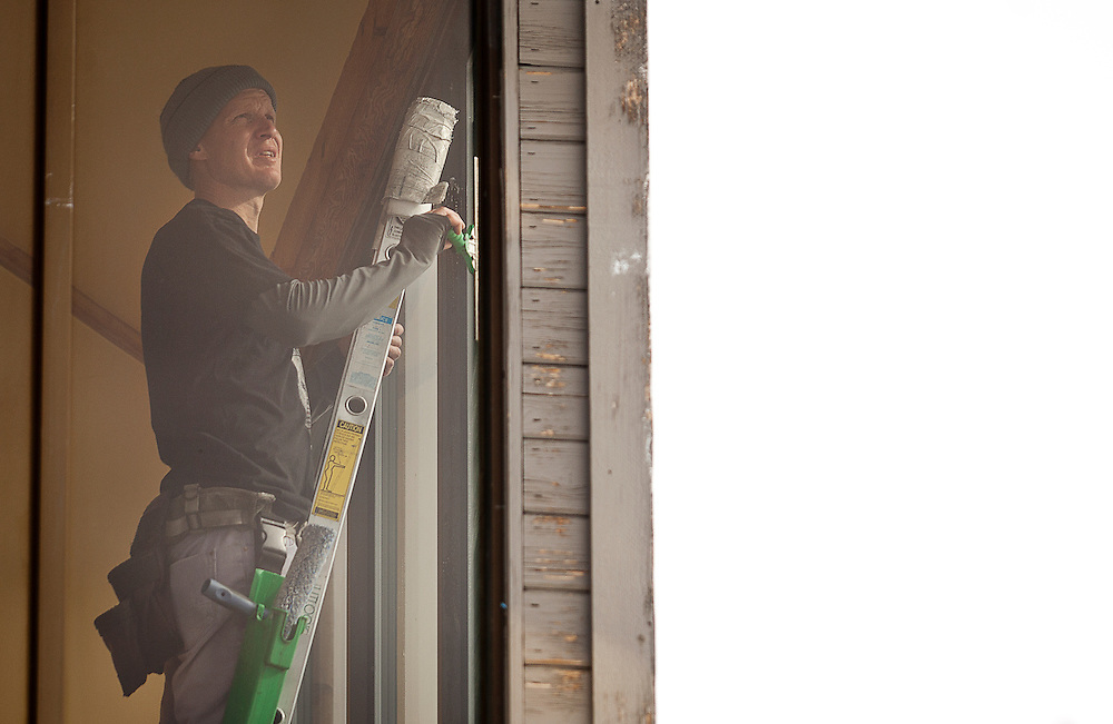 Jimmy Keithley cleans a window on the Brighton Center chalet at the Brighton Ski Resort, opening on November 13th for the season, Monday, Nov. 12, 2012.