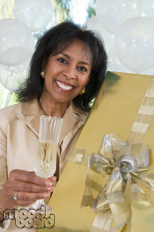 Woman holding gift and glass of champagne
