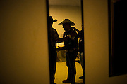 Country singer and bull riding announcer Cuiabanno Lima is prepared for his appearance at rodeo on a livestock compound  in Goiania, Brazil, Friday, Dec. 16, 2016. Considered one of the economic pillars of Brazil, hoarding increasingly huge swaths of land and spreading the same amounts of environmental degradation and land conflicts, the powerful agribusiness finds its heart, soul and voice in the city of Goiânia. Home of a million and a half souls it sits on the immense central plains of Brazil and nurtures a rodeo culture and cowboy lifestyle challenging its own urbanization, highlighting the archaic and rural character of Brazilian mindset and its society. Using cheap videoclips and broadcasting his tunes during rodeos he is invited, Lima showcases the maximum exponent of this  mentality. (Dado Galdieri for the New York Times)