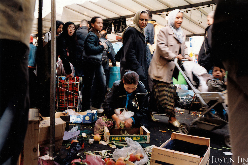France, Paris, 05-2003..An illegal Chinese woman picks disgarded vegetables from a market stall. She is part of a new wave of illegal immigrants from the Northeast of China and the country reforms is bloated state economy, laying off millions of workers.