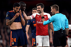 Valencia's Mouctar Diakhaby and Ezequiel Garay (left) with Arsenal's Sokratis Papastathopoulos as referee Clement Turpin gestures to them