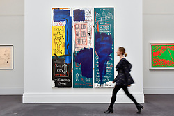 "© Licensed to London News Pictures. 23/06/2017. London, UK. A staff member walks in front of ""Untitled"", 1983, by Jean-Michel Basquiat (estimate GBP4-6m) at the preview of Sotheby's Contemporary Art Sale in New Bond Street.  The auction, which is dominated by Pop art, takes place on 28 June. Photo credit : Stephen Chung/LNP"