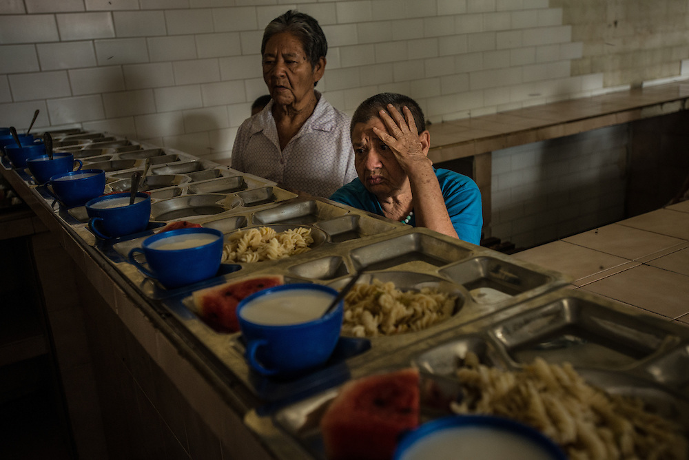 BARQUISIMETO, VENEZUELA - JULY 28, 2016: Patients wait to eat lunch: pasta, milk and a slice of watermelon, in the women's ward. The economic crisis that has left Venezuela with little hard currency has also severely affected its public health system, crippling hospitals like El Pampero Psychiatric Hospital by leaving it without the resources it needs to take care of patients living there, the majority of whom have been abandoned by their families and rely completely on the state to meet their basic needs. The hospital has not employed a psychiatrist for over two years. The halls are filled with sounds of patients crying or screaming, and an overpowering stench of urine and feces. There is a shortage of food, and drugs used to combat bipolar disorder, epilepsy, schizoaffective disorder and chronic anxiety are now in short supply, as are numerous sedatives and tranquilizers needed to care for patients. PHOTO: Meridith Kohut