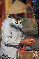 A woman selling homemade delicacies on the streets of the old town of Hoi An, Vietnam