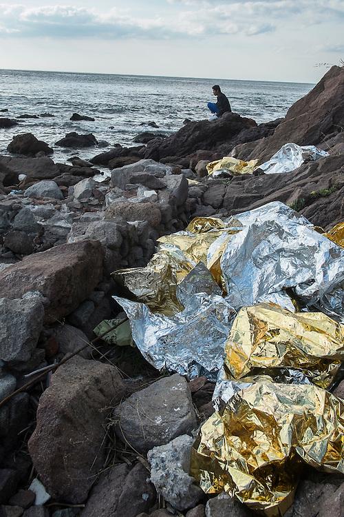 GRIECHENLAND, Lesbos, Mithymna/Molivos, 28.10.2015 / Refugee am Strandufer: In der Nacht zuvor kam es zu einem schweren Bootsunglueck vor der Kueste. Rettungskraefte konnten mindestens 242 Menschen retten, waehrend elf Menschen nur noch tot gebogen werden konnten. Die Kuestenwache geht davon aus, dass die Zahl der Toten noch deutlich steigen wird. Nachdenklich sitzt ein Mann - hinten im Bild - eine halbe Stunde allein auf diesem Felsen und kaut auf Sonnenblumenkernen. Schutzfolien liegen lose am Strand herum.