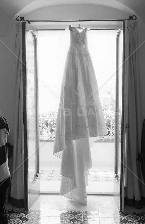 wedding dress hanging on a rod in front of french doors