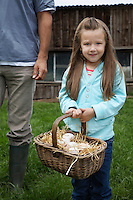 Girl (5-6) holding egg basket father (low section) standing nearby outdoors portrait