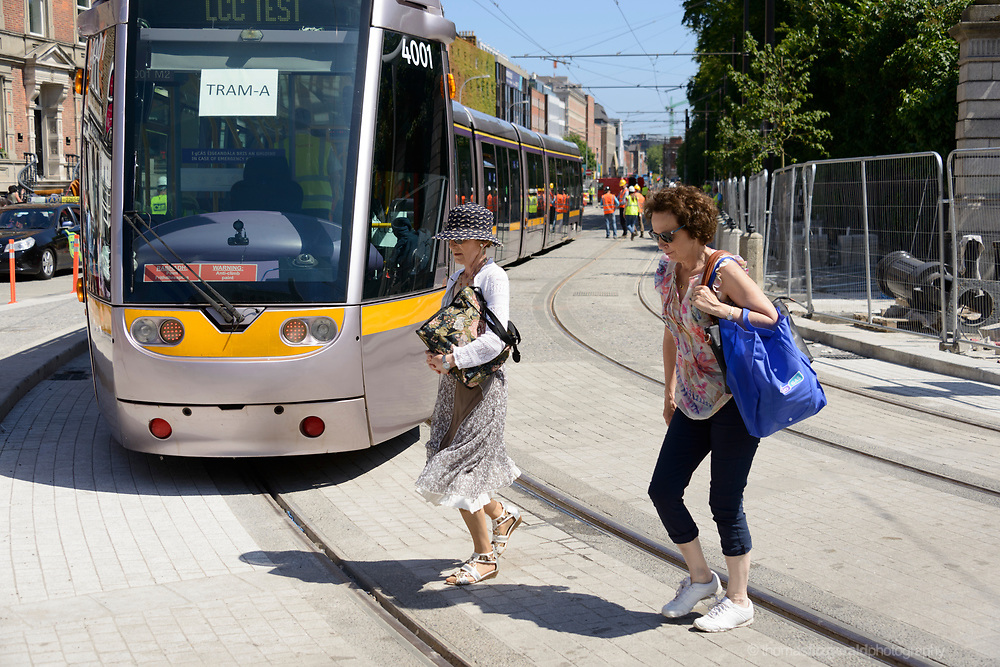 Two women cross infront of the Luas which is undergoing testing - June 17th, 2017. Dublin, Ireland. At Stephen's Green, the Cross City Luas project undergoes testing with a full tram on the newly completed tracks. A contingent of engineers walks with the tram and they carry out various checks as members of the public look on and watch the going on. The cross city Luas project is a four year project conducted to join up the two existing tram lines in Dublin city, and bring trams  and passengers from the south side to the north side on the Luas system.