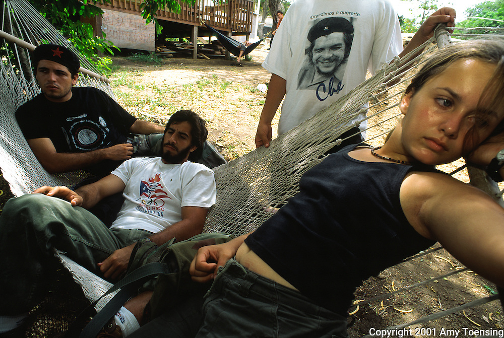 VIEQUES, PR - AUGUST 10: University of Puerto Rico students take a break from protesting the U.S. Navy performing bombing exercises on Vieques Island off the east coast of Puerto Rico on August 10, 2001. The Navy began using the island as a practice range in 1947. This use was an ongoing source of controversy with the Navy asserting its need to conduct ordinance training and the protesters claiming the exercises harm the environment and the health of the island's 9500 residents. The Navy officially stopped bombing the island in May of 2003 in response to protests like these. Puerto Rico was an outpost of Spanish colonialism for 400 years, until the United States took possession in 1898. Today Puerto Rico's Spanish-speaking culture reflects its history - a mix of African slaves, Spanish settlers, and Taino Indians. Puerto Ricans fight in the U.S. armed forces but are not entitled to vote in presidential elections. They passionately debate their relationship with the U.S. with about half the island wanting to become the 51st state and the other half wanting to remain a U.S. commonwealth. A small percentage feel the island should be an independent country. While locals grapple with the evils of a burgeoning drug trade and unchecked development, drumbeats still drive the rhythms of African-inspired bomba music. (Photo By Amy Toensing) _________________________________<br />