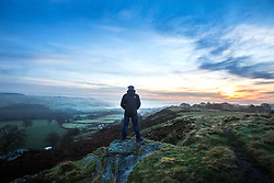 © Licensed to London News Pictures. 12/12/2016. Baildon UK. A man stands on top of Baildon Moor looking down on the fog covered town of Shipley in Yorkshire at sunrise this morning. Photo credit: Andrew McCaren/LNP