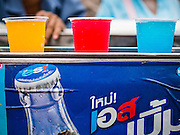 """09 AUGUST 2014 - BANGKOK, THAILAND:     Colored soft drinks for sale at the entrance to the Ruby Goddess Shrine in the Dusit section of Bangkok. The seventh month of the Chinese Lunar calendar is called """"Ghost Month"""" during which ghosts and spirits, including those of the deceased ancestors, come out from the lower realm. It is common for Chinese people to make merit during the month by burning """"hell money"""" and presenting food to the ghosts. At Chinese temples in Thailand, it is also customary to give food to the poorer people in the community.   PHOTO BY JACK KURTZ"""