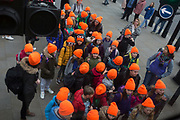 Schoolchildren wearing distinctive orange hats wait to cross Parliament Square, on 19th March 2019, in London, England.