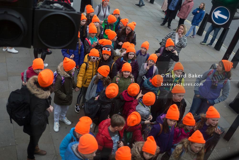 Schoolchildren wearing distinctive orange hats wait to cross Parliament Square, on 19th March 2019, in London, England.