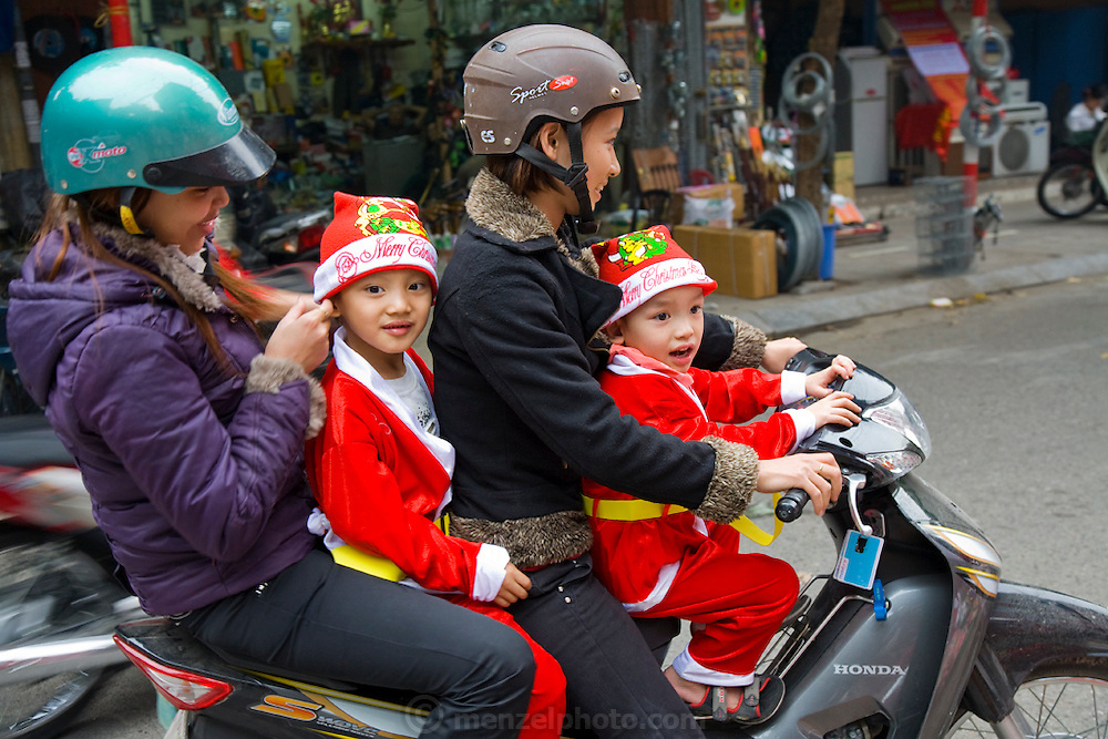 Women carry girls in Christmas colors on a motorcycle in Hanoi, Vietnam.