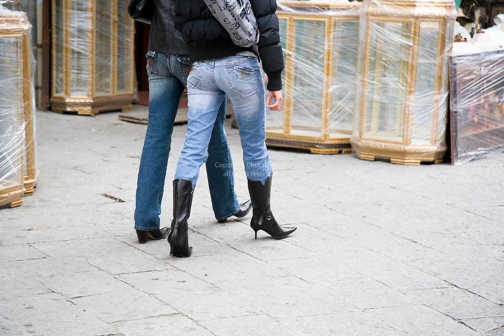 Two women wearing black leather boots shop at the outdoor market on Via Bandiera, Palermo, Sicily, Italy
