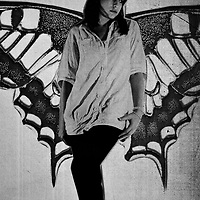 A young woman standing infront of a butterflies wings